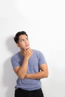 Смотреть молодого азиатского человека думая вверх изолированный