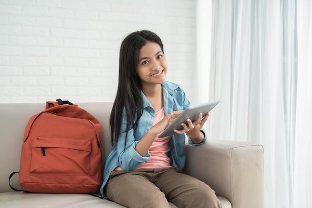 Младший школьник сидит на диване с планшетом