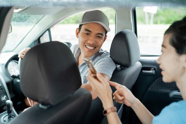 Женщина пассажир показывает смартфон, чтобы соответствовать месту и месту назначения