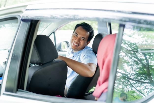 Мужчина-водитель выглядит улыбающимся и счастливым в чате с пассажиром хиджаба