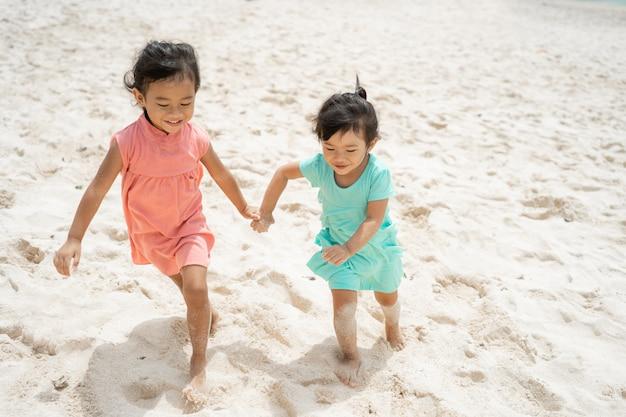 Два маленькая девочка работает с рукой держать удовольствие играть вместе
