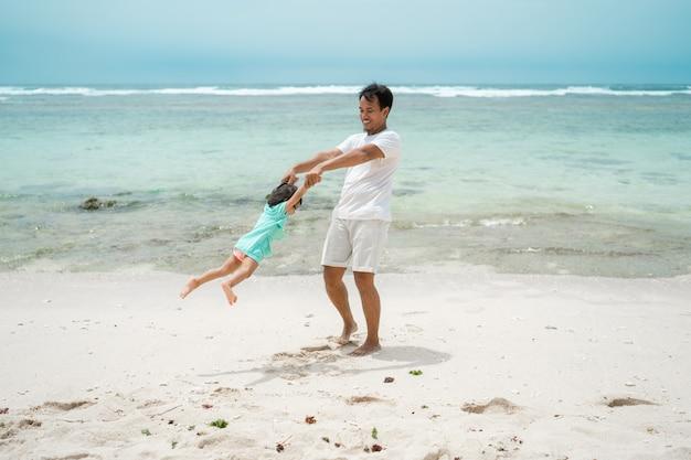 スイングをするときに娘の手を握って父がビーチで回転します