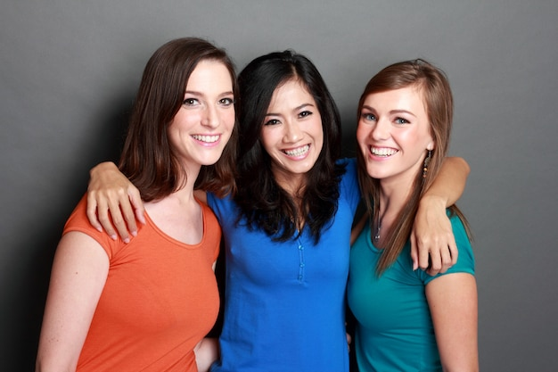 Три молодые женщины обнимаются