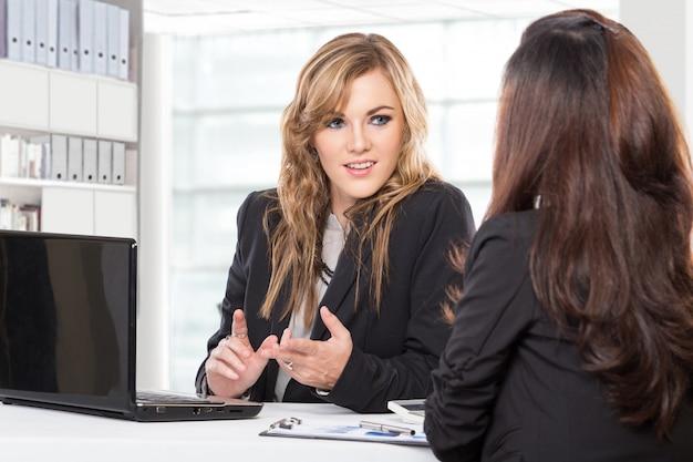 Две дружелюбные деловые женщины сидят и обсуждают новые идеи, используя портативный компьютер