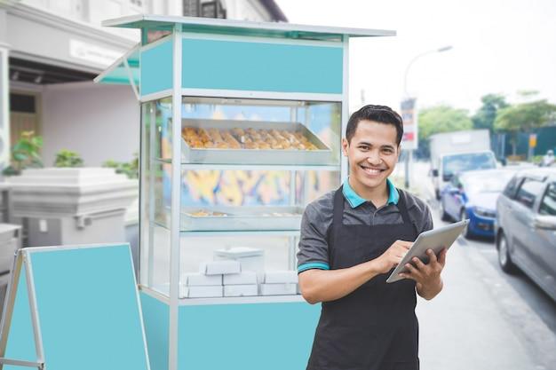 Мужской предприниматель с прилавком с едой