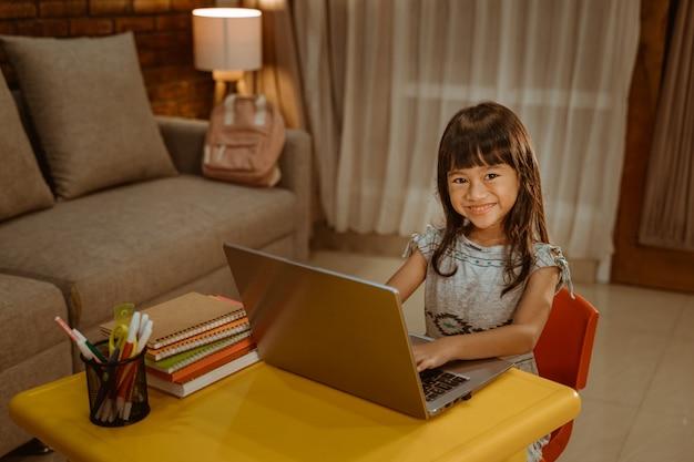 ラップトップを使用して宿題をやって幸せな少女