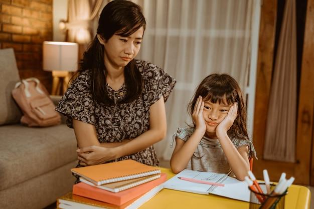 Усталый ребенок делает домашнее задание вечером