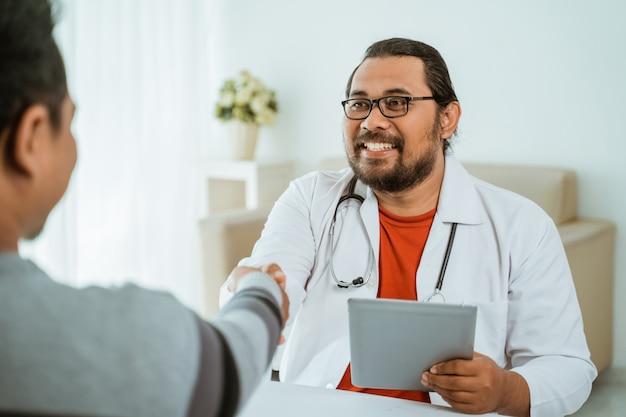 彼のオフィスで患者と手を振って笑顔の医者