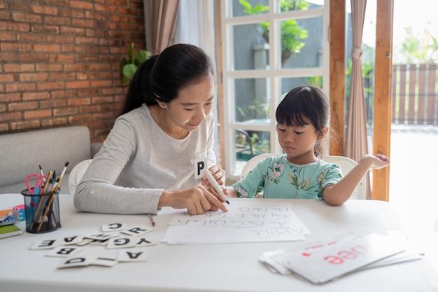 母は彼女の娘に読み書きの基本を教える