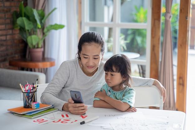 携帯電話で勉強する母と娘
