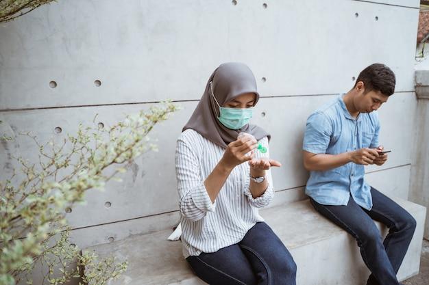 Мусульманская женщина с помощью дезинфицирующего геля для рук