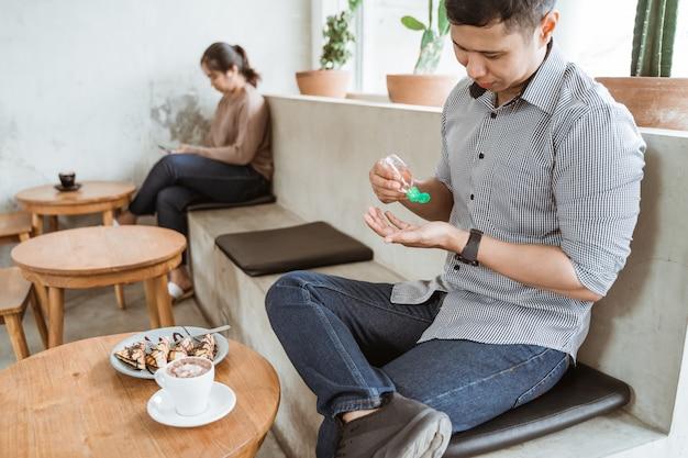 Человек, применяя дезинфицирующее средство для рук в кафе