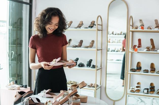 Женщина выбирает некоторые туфли на полках в магазине модной одежды