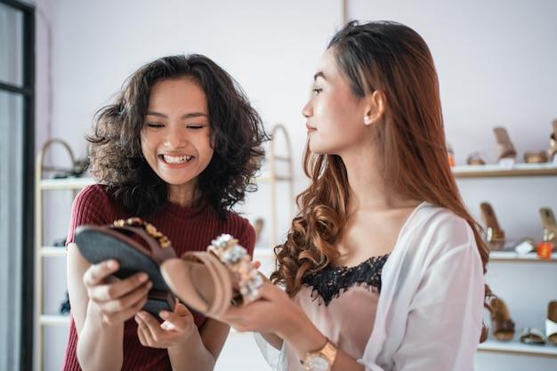 Женщина и друг в магазине модной одежды выбирают обувь