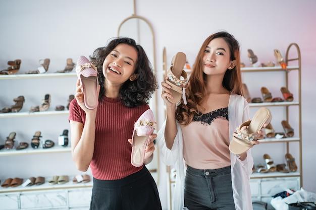 Мода, шоппинг, две девушки, наслаждающиеся сбором обуви