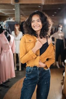 Женщина в повседневной джинсовой куртке позирует в магазине моды