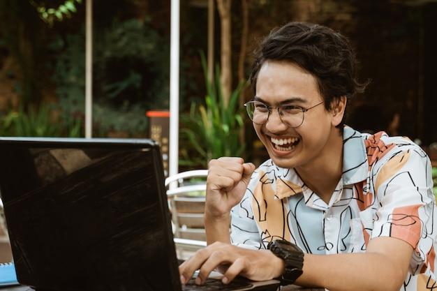 アジアの若者がノートパソコンのモニターを見て、リラックスして座っていると笑う