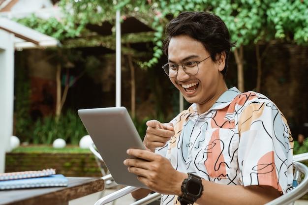 Азиатская молодежь в очках держит и смотрит на экран планшета, а затем смеется, когда сидит расслабленно