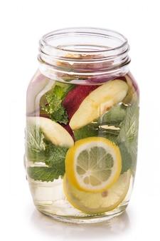 レモン、リンゴ、ミントの葉の新鮮なフルーツ水を注ぎました。隔離する
