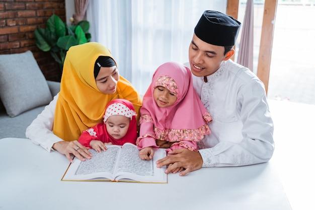 アジアの家族が一緒にコーランを読んで