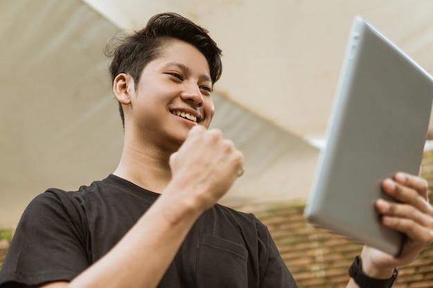 Азиатская молодежь смотрит на экран планшета и смеется