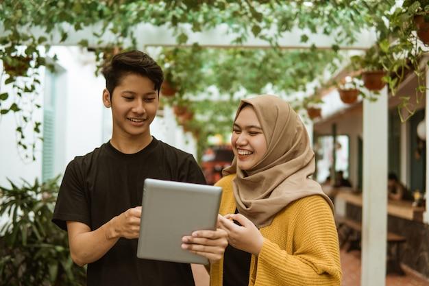 Азиатский мужчина и хиджаб девушка, указывая на экран планшета