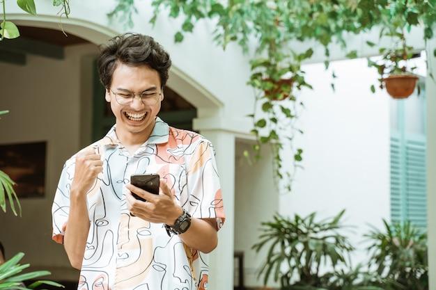 Азиатская молодежь, держащая и смотрящая на мобильные телефоны, очень счастлива