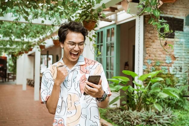 Молодежь смеется, держа мобильный телефон