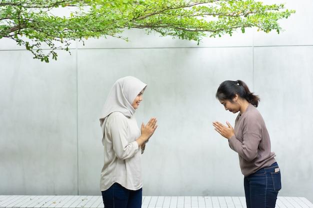 Два друга с приветственными жестами приносят свои извинения