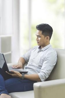 Молодой человек, используя ноутбук, сидя на диване у себя дома