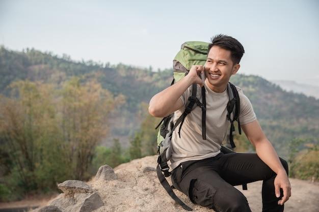 Мужской турист с помощью мобильного телефона