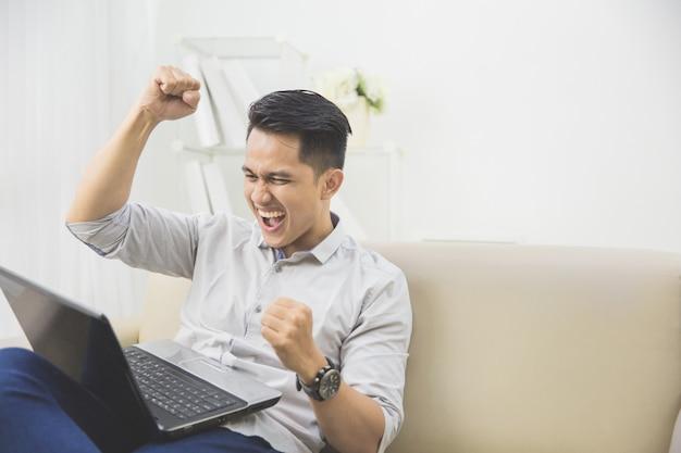 Счастливый молодой человек поднять руку. успех