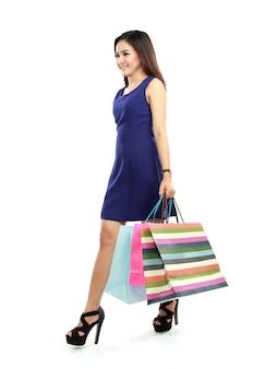 Полная длина боковой вид молодой женщины, ходьба с корзина