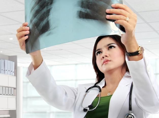 Женщина-врач в белом халате и стетоскоп, глядя на рентген