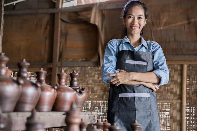 Улыбающаяся женщина-гончар гордо стоит в своей гончарной мастерской