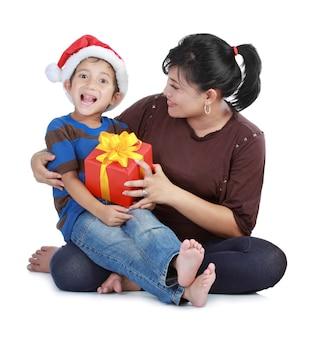 サンタクロースの帽子と彼のお母さんの少年