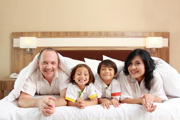 Счастливая семья на белой кровати