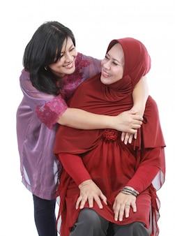 Мусульманская женщина с дочерью на белом фоне