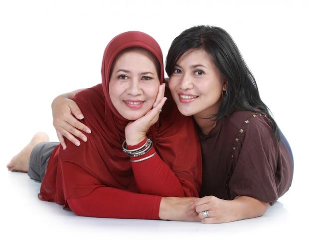 Мусульманская женщина со своей дочерью лежит на белом фоне