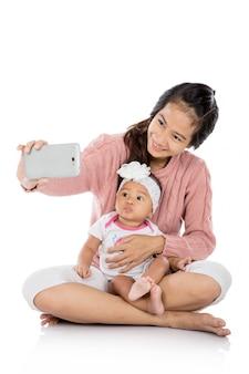 Женщина со своим ребенком, принимая селфи вместе