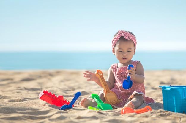 Девочка играет с игрушками на пляже