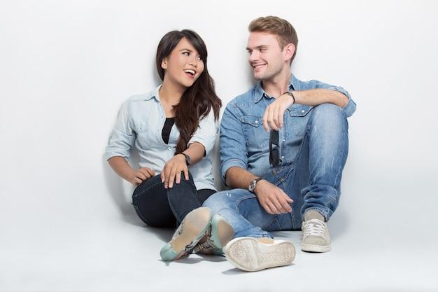 Смешанная пара, сидя на полу. мужчина обнимает женщину