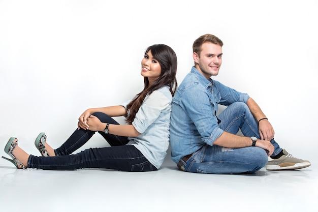 Смешанная пара сидит спиной к спине на полу