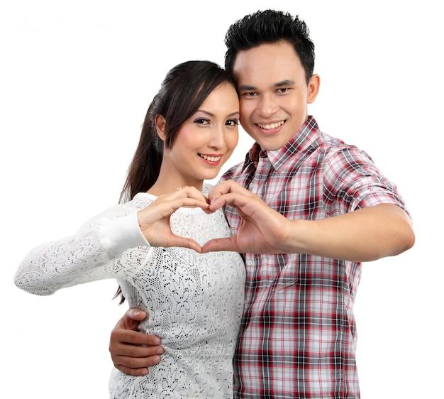 指で心を示す愛の若いカップル