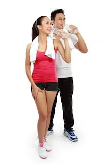 男性と女性のフィットネス後の水を飲む