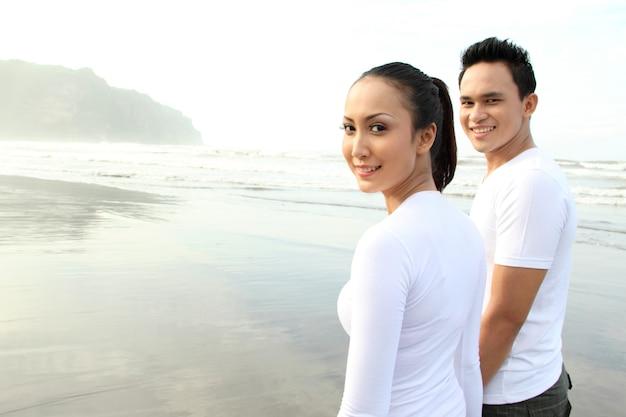 笑顔のビーチで幸せな若いカップルの肖像画