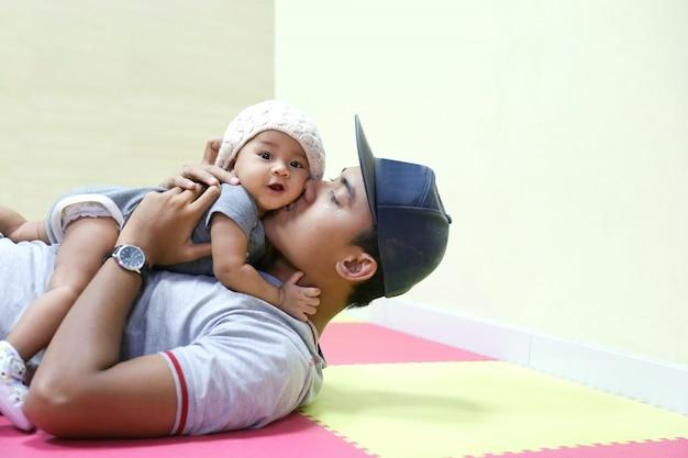 Молодой азиатский отец держа и целуя прелестного младенца
