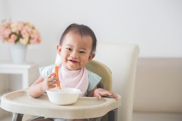 高い椅子に座っている女の赤ちゃんと彼女の自己を養う