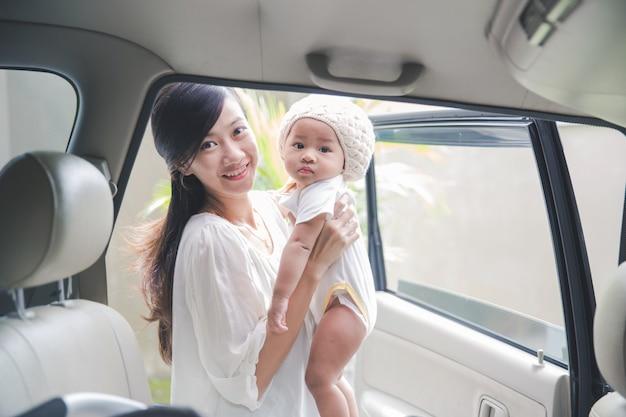 母は彼女の赤ちゃんを車の座席に置く準備ができて