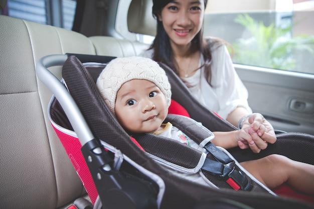 母親が車のチャイルドシートで赤ちゃんを保護